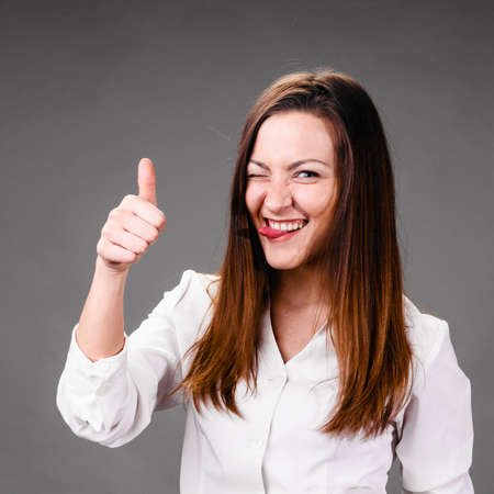 thumbs up woman: Portrait of winking and smiling business woman with thumbs up, on gray background