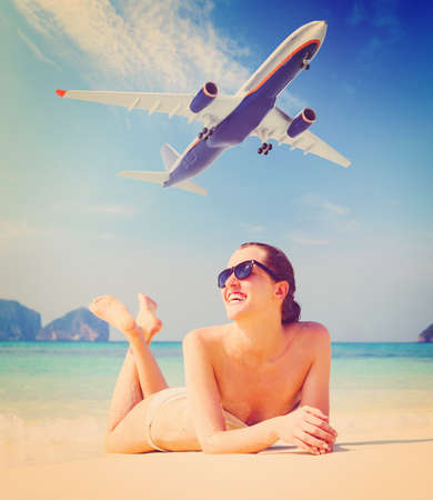 summer travel  young woman is lying on beach with aeroplane flying above photo