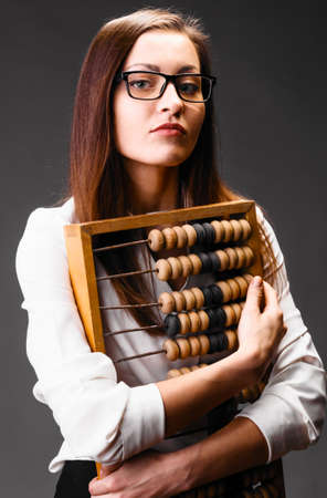 Portrait of business woman with abacus on gray background photo