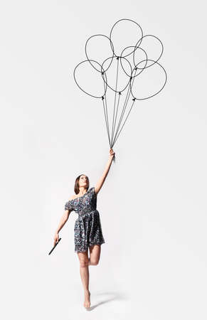 imagination  young woman is flying away with drawn balloons photo