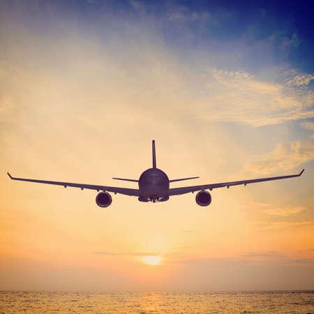 비행기는 일몰 바다 위에 날고있다