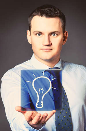 caucasian businessman is holding bulb in hands photo