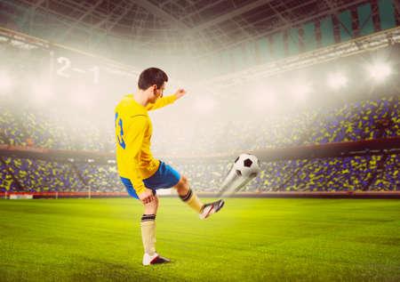 colores calidos: f�tbol o jugador de f�tbol patea la bola en el estadio, los colores c�lidos tonos Foto de archivo