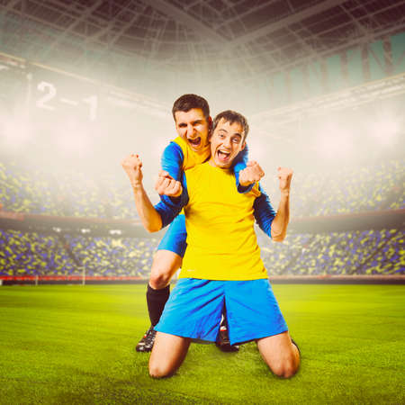 soccer or football players are celebrating goal on stadium, warm colors toned photo