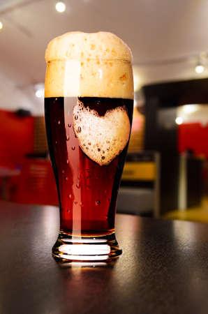 loving beer  glass of fresh draft dark beer on table in pub photo