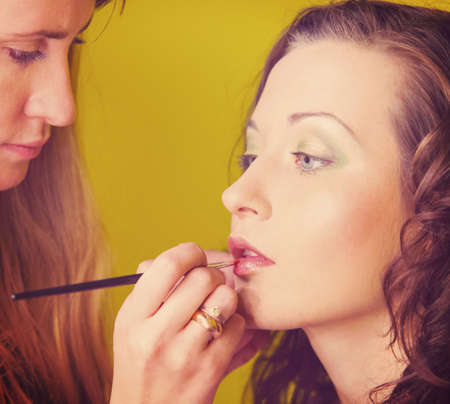 makeup artist is applying cosmetics on model face photo
