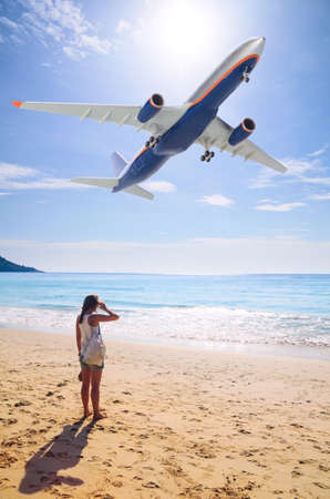 summer travel  young woman is standing on beach with aeroplane flying above photo