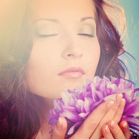 beautiful woman with big flower on blue background photo