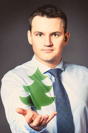 caucasian businessman is holding christmas tree in hands photo