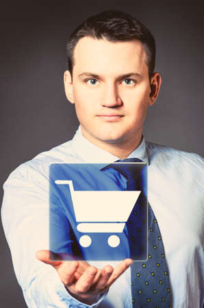 caucasian businessman is holding shopping cart in hands photo