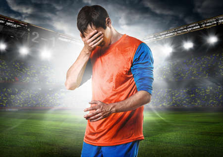 unhappy soccer or football player with palm on his face on stadium Stock Photo