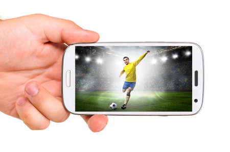 hand is holding a modern phone with soccer or football player shooting a ball on screen