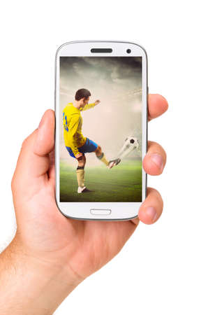 hand is holding a modern phone with soccer or football player shooting a ball on screen photo