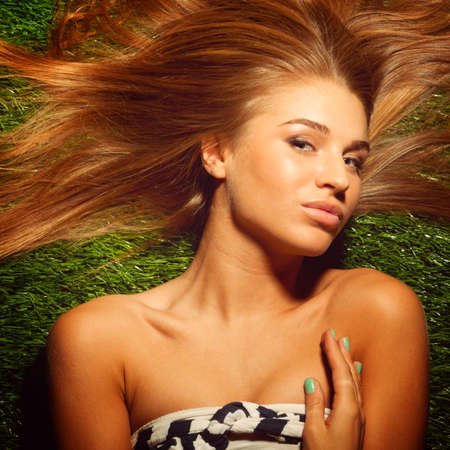 fashionable long haired woman is lying on grass photo