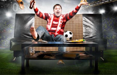 happy soccer or football fan on sofa at stadium photo