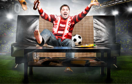 supporter: happy soccer or football fan on sofa at stadium
