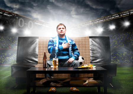 personas viendo tv: f�tbol feliz o aficionado al f�tbol con la mano en el coraz�n en el sof� en el estadio
