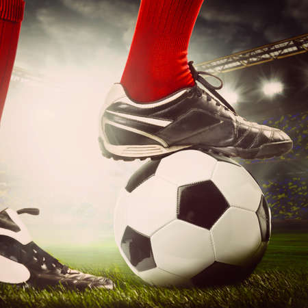 legs of a soccer or football player on ball on stadium photo