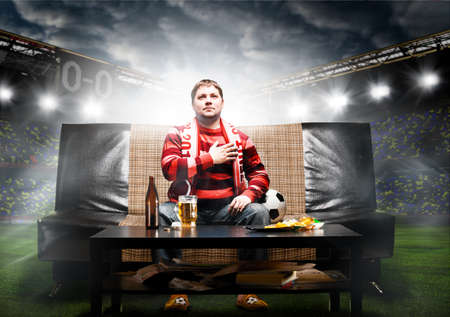 happy soccer or football fan with hand on heart on sofa at stadium photo