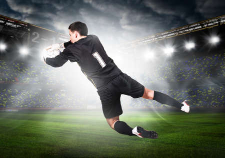 soccer or football goalkeeper is catching ball on stadium photo