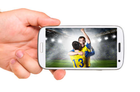 hand is holding a modern phone with soccer or football player on screen photo