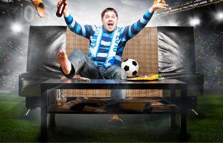 hombre tomando cerveza: f�tbol feliz o aficionado al f�tbol en el sof� en el estadio