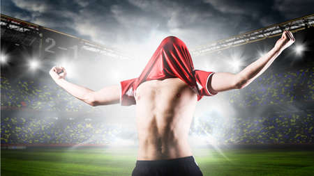 soccer or football player is celebrating goal on stadium with his jersey on head Standard-Bild