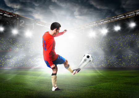 goal kick: soccer or football player is kicking ball on stadium Stock Photo