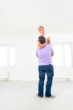 happy couple is jumping at their new empty apartment photo