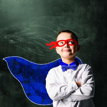 courageous: school boy wearing a superhero costume with blackboard behind him
