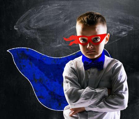 superman: school boy wearing a superhero costume with blackboard behind him