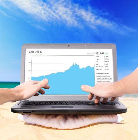 downshifting: working remotely using laptop on beach