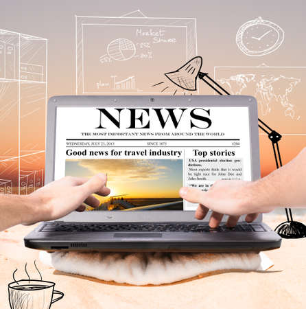 evening newspaper: working remotely in virtual office using laptop on beach at sunrise Stock Photo