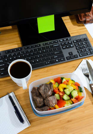 homemade lunch box at modern stylish work place, view from above photo