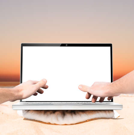 downshifting: working remotely using laptop on beach at sunrise