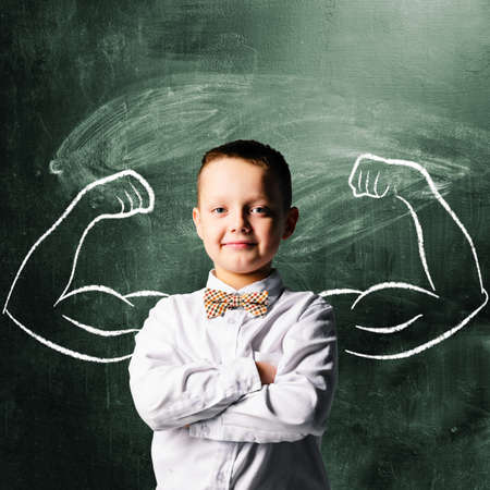 strong: school boy is standing with strong hands on blackboard behind him