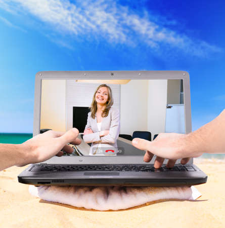 downshifting: making a video call using laptop on beach