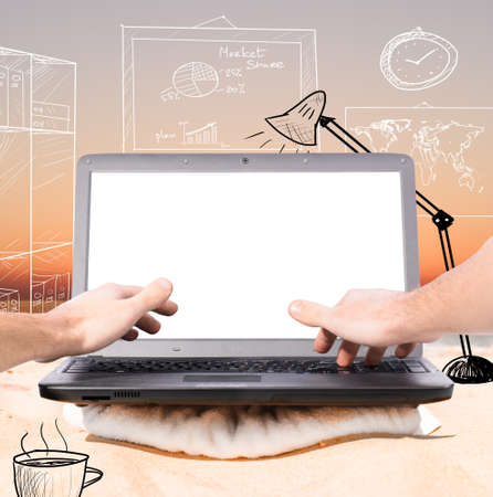 virtual office: working remotely in virtual office using laptop on beach at sunrise Stock Photo
