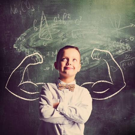 業務: 學校的男孩站在有力的手在黑板上身後