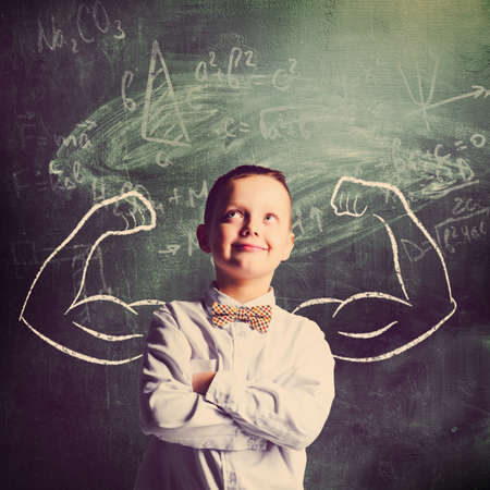 school boy is standing with strong hands on blackboard behind him Stock Photo - 41812245