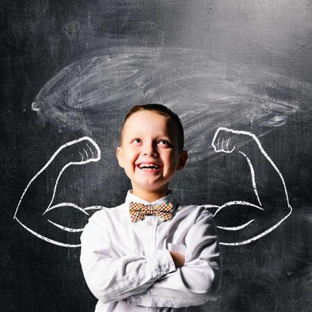 hombre fuerte: niño de la escuela está de pie con las manos fuertes en la pizarra detrás de él Foto de archivo