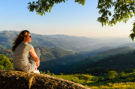 viewing: scenic view of woman watching at sunset mountains, Peneda-Geres National Park, northern Portugal.