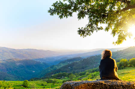 sunrise field: scenic view of woman watching at sunset mountains, Peneda-Geres National Park, northern Portugal.