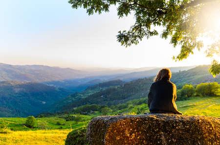 vista panorámica de la mujer que mira en las montañas puesta del sol, parque nacional de Peneda-Geres, en el norte de Portugal. Foto de archivo