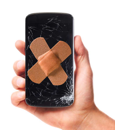 male hand is holding modern smartphone with cracked screen in one corner healed with plaster, isolated on white background 스톡 콘텐츠