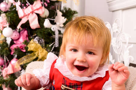 baby near christmas tree: cheerful baby near christmas tree Stock Photo