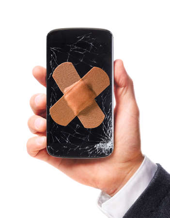 healed: male hand is holding modern smartphone with cracked screen in one corner healed, isolated on white background Stock Photo