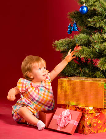 baby near christmas tree: baby is reaching for christmas toy near tree