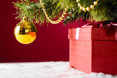 under the tree: gift box on snow under christmas tree