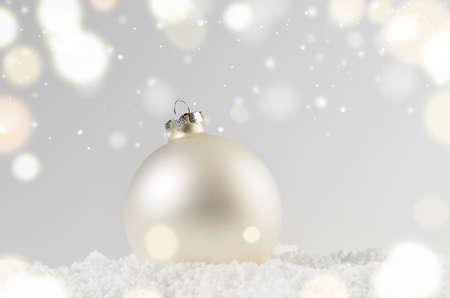 witte decoratieve kerst bal op sneeuw tegen de grijze feestelijke achtergrond